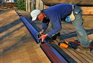 A worker laying caulk along a ridge vent.