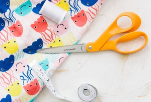 heating pad fabric with colorful jellyfish pattern and sewing supplies like scissors, thread and measuring tape