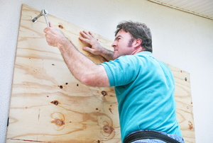 A man uses plywood to board up a window.
