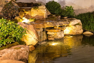 A backyard pond with lights and a waterfall