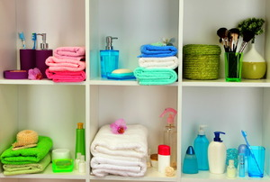 Hand towels and soaps neatly organized on bathroom shelves.