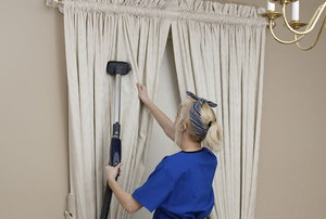 A woman cleans drapes.
