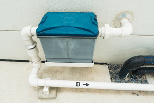 A grease trap installed on a pipe outside the home.