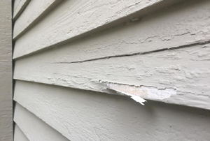 Peeling paint on house siding.