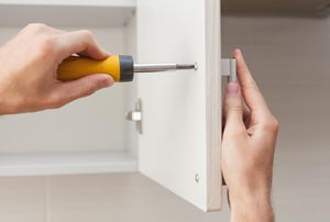 screwing a handle onto a white cabinet