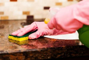 A close-up of gloved hands cleaning a granite countertop.