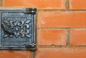 metal flue vent with floral design in brick wall