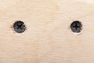 two screws embedded in a plank of wood