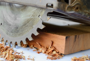A circular saw cutting a wood plank.