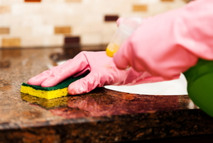 pink gloved hands cleaning granite