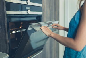 A woman opening up an oven door.