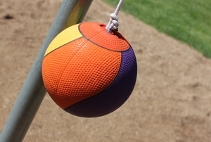 An orange tetherball hanging from a rope on a galvanized pole surrounded by dirt.