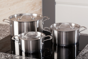 A set of three aluminum pots sitting on a stove top.
