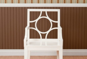 a chair in front of a wall with molding and line patterns