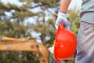 contractor with orange hardhat in hand