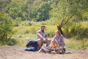 A couple sitting around a campfire during the day with green trees in the background.