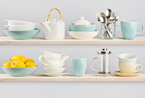 Open kitchen shelving with bowls, cups, and silverware.