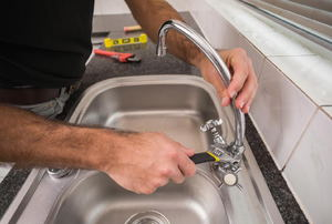 A man replacing a sink faucet.