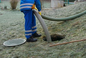 man with hose pumping out a septic tank
