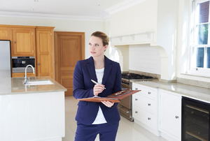 A female realtor standing in a kitchen with a clipboard.