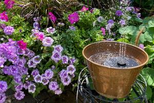 flower garden with solar fountain in brass bucket