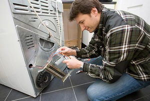 A technician working on repairing issues with a dryer.