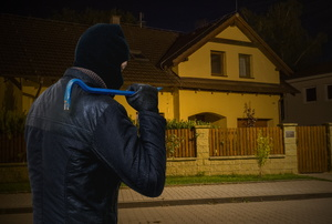 A burglar looking at a house at night.