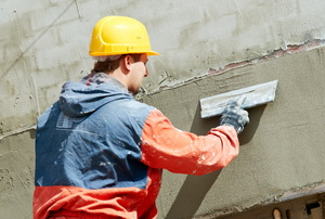 A construction worker applying stucco on a wall.