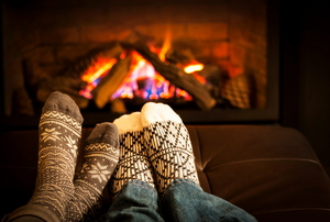 A pair of socked feet in front of a fire.