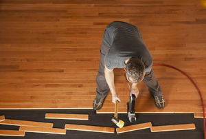 A man installing wood flooring with a pneumatic nailer.