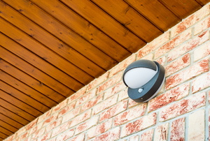 A motion sensor light on a brick home.