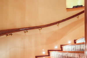 A lit, curved stairway with a handrail mounted on the wall.