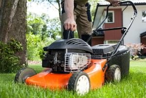 An orange lawnmower on grass.