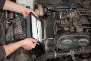 A pair of hands replacing an air filter in a car.