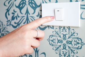 pushing a light switch on a wallpapered wall.