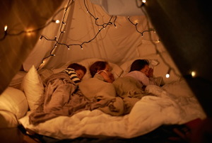 Kids asleep in a blanket fort.