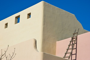 An adobe house with a ladder leaning against one the levels.