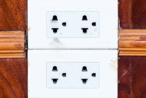 A dual wall outlet set into a wood paneled wall.