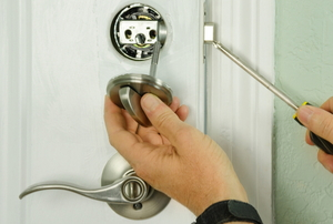 hands installing disassembled deadbolt lock