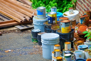 Various cans of old paint, set aside for disposal.