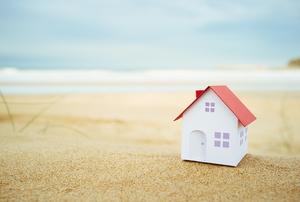 A small white house on a sandy beach.