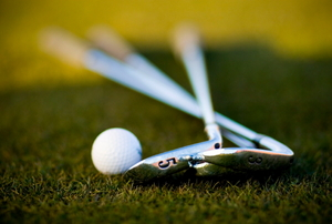 Two golf clubs lying next to a golf ball on green grass.