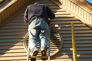 A homeowner on a ladder, painting his vinyl siding.