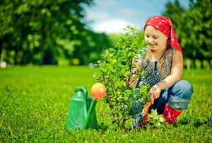 A little girl planting a tree on Earth Day.