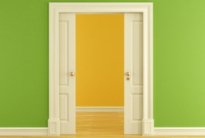 a pocket door between a yellow and green room