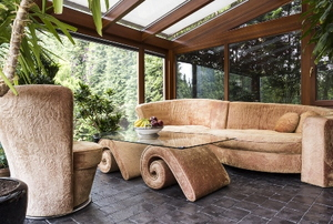 sunroom with natural design elements including couch, coffee table and large plant