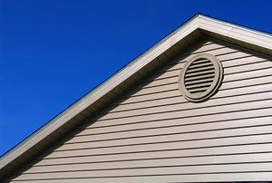 Exterior view of a gable vent with a blue sky in the background.