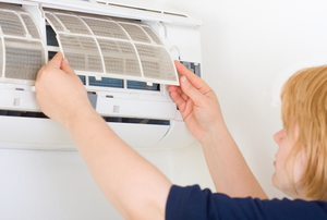 A woman installs a split heat system.