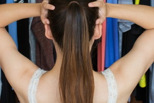 a woman holding her head looking into a full closet
