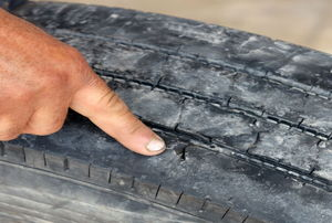 A man points to dry rot on a tire.